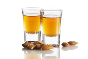 Italian Amaretto liquor and almonds isolated on white